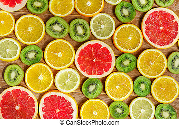 frame with slice of oranges, lemons, kiwi, grapefruit pattern isolated on wooden background. Flat lay, top view