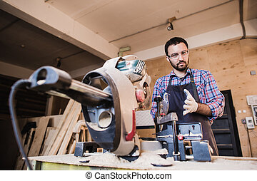 Framing contractor using a circular cut off saw to trim wood studs length.