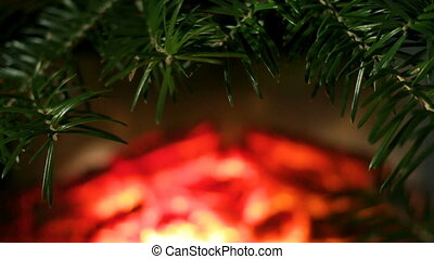 Framing spruce branches on a background of fire in the fireplace. A cozy scene as a blank for animated decoration of a Christmas or New Year