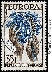 frança, -, circa, 1957:, um, selo, impresso, em, a, frança, mostra, mãos, com, símbolos, de, agricultura, e, indústria, unidas, europa, para, paz, e, prosperidade, circa, 1957