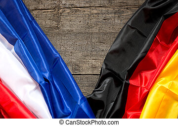 France and Germany Flag on a wooden Background