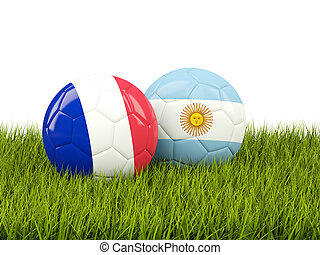 France vs Argentina. Soccer concept. Footballs with flags on green grass