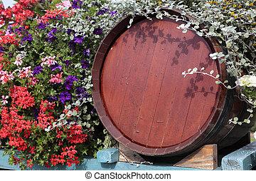 France wood wine barrel with flower display at grape harvest time.
