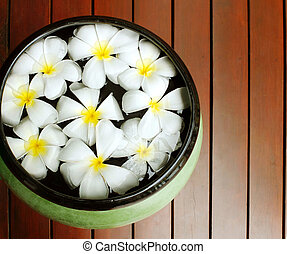 Frangipani flowers floating in the ancient bowl