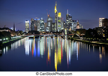 Image of Frankfurt skyline after sunset with the reflection of the city in Main River.