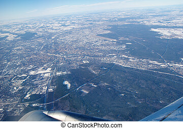 FRANKFURT, GERMANY - JAN 20th, 2017: View through aircraft window onto jet wing, wingview over snow covered city of Frankfurt am Main, airport FRAPORT in the background
