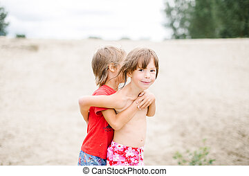 Fraternal twins hugging at the beach while playing on hot summer day