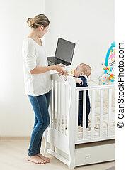 frau, arbeitende , nehmen, junger, baby, laptop, sorgfalt