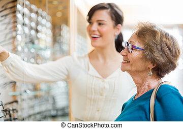 frau, assistieren, älter, kunde, in, auswählen, brille