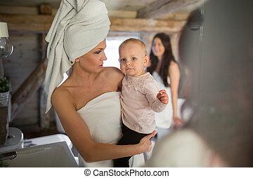 frau, aufgewickelt, in, handtücher, halten baby