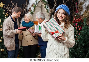 frau besitz, weihnachtsgeschenk, mit, familie hintergrund