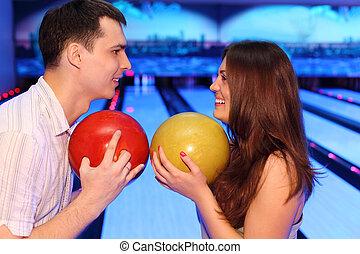 frau, blick, bowlingspiel- kugeln, mann, jedes, halten, andere, glücklich