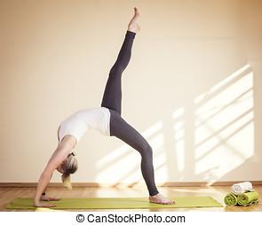 Frau die Yoga macht im stehen auf Yogamatte