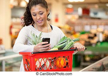 frau- einkaufen, handy, gebrauchend, lächeln, kaufmannsladen