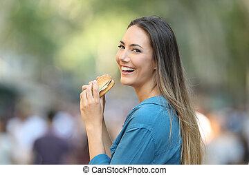 frau essen, a, hamburger, anschauen, sie, in, der, straße