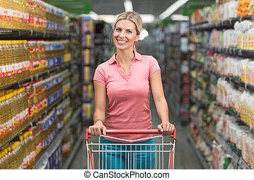 frau, fahren, einkaufswagen, während, lebensmittelgeschäft, in, supermarkt