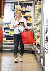 frau, gebrauchend, digital tablette, gehen, in, supermarkt