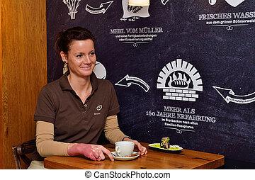 Frau geniesst Tasse Kaffee - junge Frau erholt sich bei...