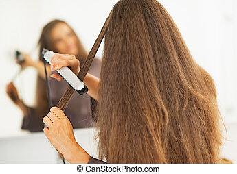 frau, gerade machen, straightener, haar, hintere ansicht
