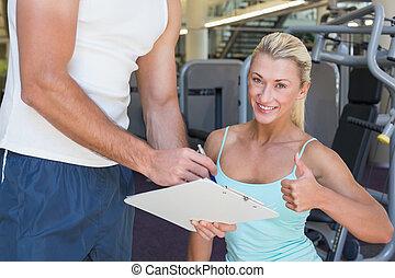 frau, gesturing, daumen hoch, besides, trainer, mit, klemmbrett, an, turnhalle