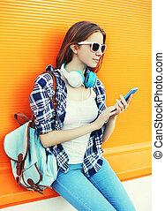 frau, hört, zu, musik, in, kopfhörer, gebrauchend, smartphone, aus, bunte, hintergrund