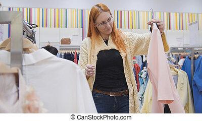 frau, in, brille, untersucht, a, rosa kleid, in, kleidung frauen, kaufmannsladen