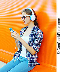 frau, in, kopfhörer, hört, zu, musik, gebrauchend, smartphone, aus, bunte, hintergrund