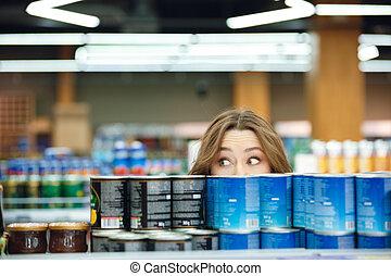frau, junger, supermarkt, lebensmittel, pflückend, beiläufig