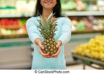 frau, mit, ananas, an, lebensmittelgeschäft