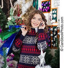 frau, mit, einkaufstüten, gebrauchend, cellphone, in, kaufmannsladen