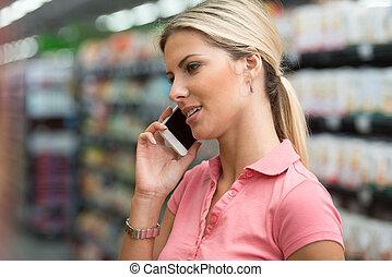 frau, mit, handy, in, a, supermarkt