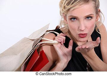 frau, mit, kaufmannsladen, säcke, blasen kusses, kamera