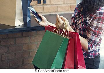 frau, mit, shoppen, bags., gebrauchend, beweglich, smartphone, für, online-bankwesen, in, draußen, shoppen, mall., alles, auf, beweglich, schirm, ar, design, auf.