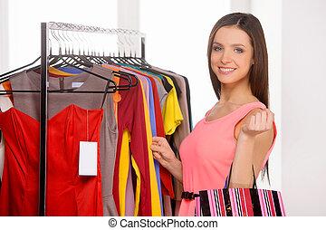 frau, shopping., schöne , junge frau, wählen, kleiden, in, einzelhandelsgeschäft