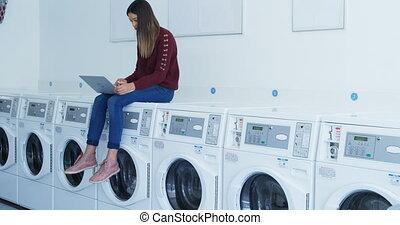 frau sitzen, auf, waschmaschine, und, laptop benutzend, 4k