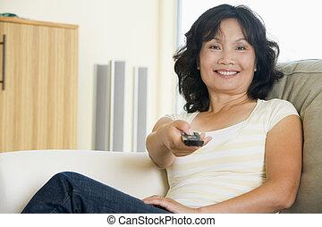 frau sitzen, in, wohnzimmer, besitz, fernsteuerung, lächeln