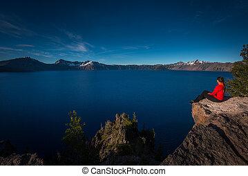 frau sitzen, rand, von, a, felsformation, anschauen, kratersee, oregon