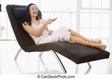 frau sitzen, stuhl, gebrauchend, fernsteuerung, lächeln