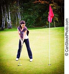 frau, spielen golf spieler, training, setzen, kugel grün, zu, becher