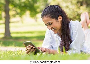 frau, textmessaging, während, entspannend, park