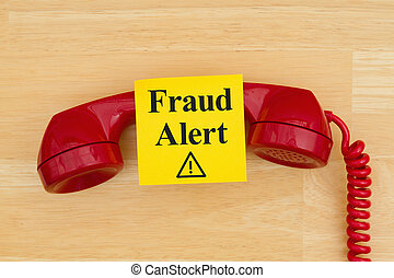 Fraud alert on sticky note with a retro red phone on textured wood desk