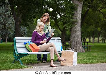 frauen, mit, einkaufstüten, gebrauchend, tablette pc, an, park