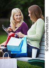 frauen, mit, einkaufstüten, gebrauchend, tablette pc, draußen