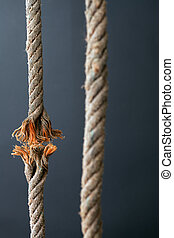 Cut and frayed rope hanging by a thread and ready to break on dark background