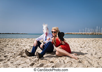 Freaky guy in suit and funny mask sits with beautiful girl in red dress