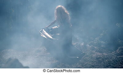 Freaky young woman dancing in the thick blue smoke on the...
