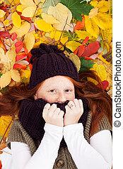 Freckled girl in leaves
