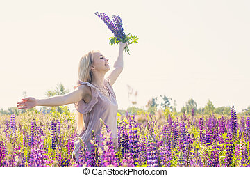 Free and happy woman with bouquet of lupines
