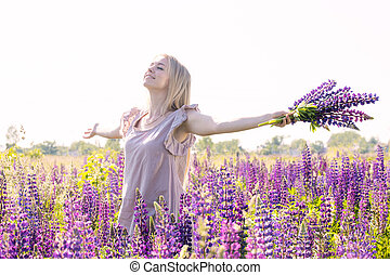 Free and happy woman with bouquet of lupines on the field