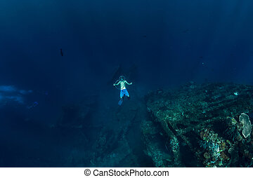 Free diver in the depth make bubble ring near USS Liberty Wreck